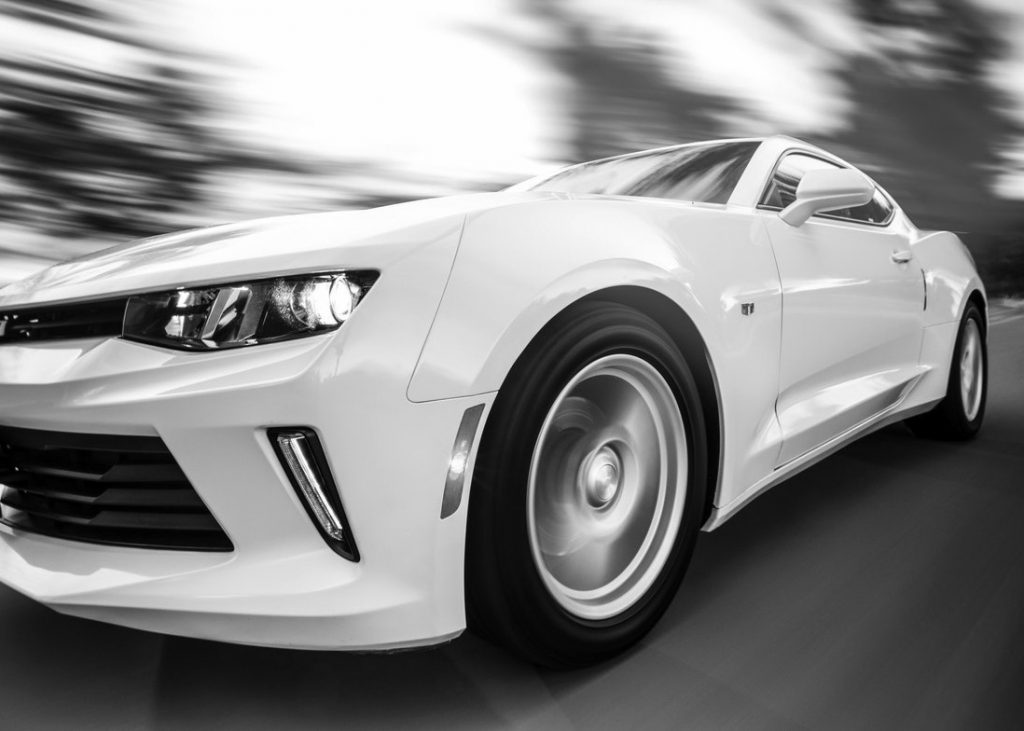Speeding white car on blurry background